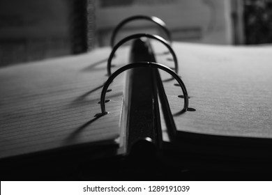 Black and White Image of a Three Ring Binder Illuminated by a Desk Light During the Late Night Hours Close Up Frontal View