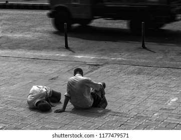 Black and White image of Two Men Sitting on a Sidewalk