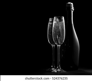 black and white image of two wine glasses with champagne and a bottle of champagne, the outlines and highlights, black background