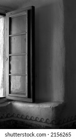 Black and white image of warm light washing through an open window in the Mission of Santa Barbara