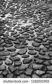 a black and white image of water pooled on a stone roadway