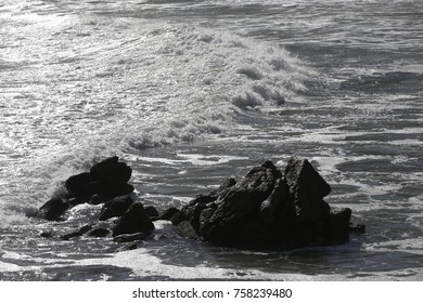 Black and white image of waves crashing on rocks near the beach