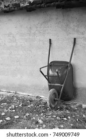 Black and white image of a wheelbarrow leaning against a wall with leafs on the grass.