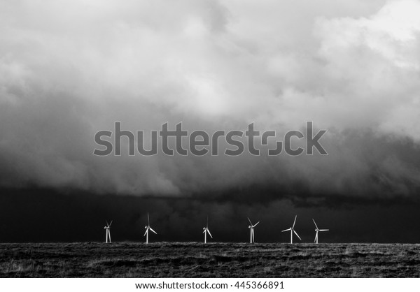 Black and white image of wind power turbines with large storm overhead Power vs Power