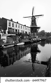 Black and white image of windmill and canal in the Netherlands