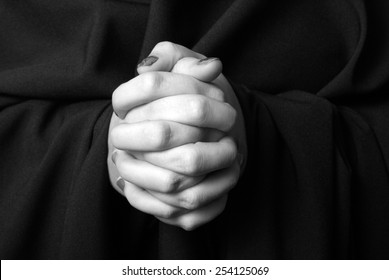 A black and white image of a womans hands clasped in prayer.