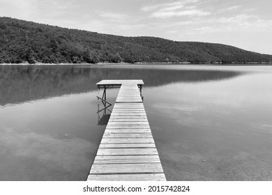Black and white image of a wooden deck pier over a lake between hills.