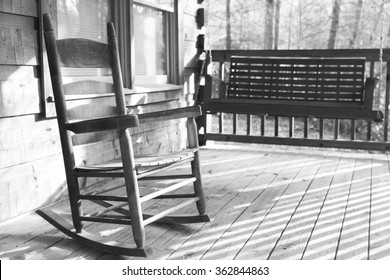 Black and white image of a wooden rocking chair on a porch of a log cabin with a wooden swing blurred in the background