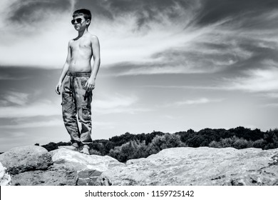 Black and white image of a young caucasian boy, wearing camo pants and sun glasses, standing on rocks near a beach in Bibione, on the Adriatic Sea, Italy