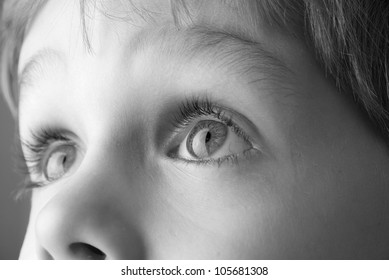 Black and white image of a young child looking up.