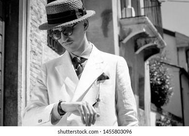 Black and white image of a young dandy wearing a tie, a red pocket handkerchief and a straw boater hat, checking the time in the streets of an Italian town