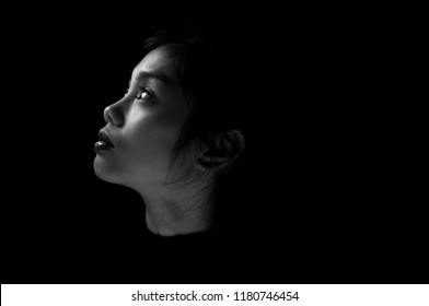 Black and white image of young girl facing single light on black background.