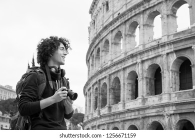 Black and white image of young tourist with a camera and backpack taking pictures of Colosseum in Rome, Italy. Young tourist taking pictures of Colosseum