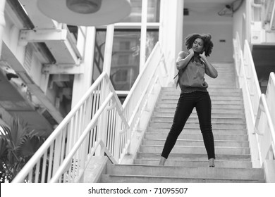 Black and white image of a young woman posing on a staircase