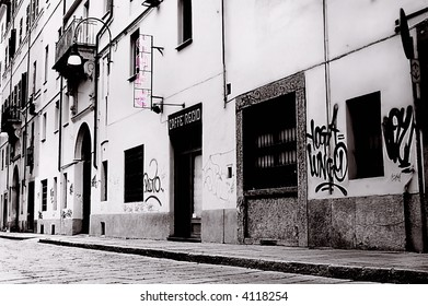 Black and White imagery of a sidestreet in Italy,the word CAFE in pink lights.