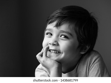 Black and white indoor portrait of adorable little boy sitting alone and looking at camera with smiling face, Low key Head shot Happy kid relaxing at home, Positive child with a happy face