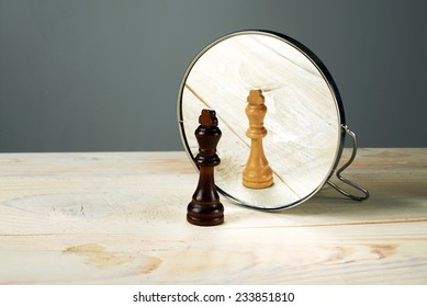 Black or white king chessmen in front of the mirror, concept about racism.