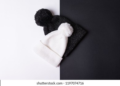 Black and white knitted beanie hats. Closeup, flat lay, no retouch. Contrast fashion concept.