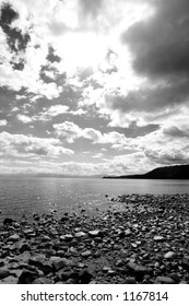 Black and white of lake, clouds and rocky shoreline
