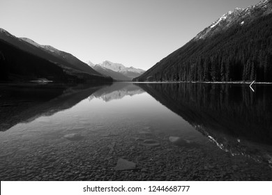 Black and white landscape of a British Columbia, Canada Lake with Mountains in background reflecting into calm and smooth water