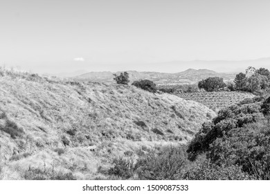 Black and white landscape of California mountains in dry late summer with city in distance