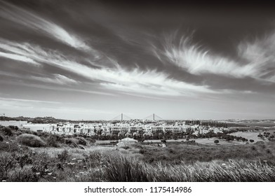 black and white landscape of Costa Esuri, Ayamonte urbanisation and the International bridge over the Guadiana River between Spain and Portugal