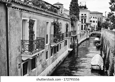 A black and white landscape image of a canal in Venice, Italy with boats moored along the side. A foot bridge is seen and is reflected in the still water