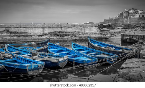 Black and white landscape of moroccan Essaouira harbor with selective blue boats