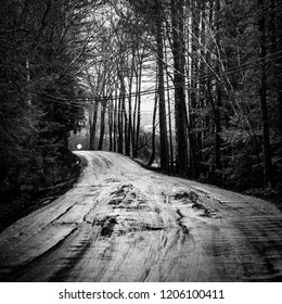 Black and white landscape photograph of muddy dirt road.