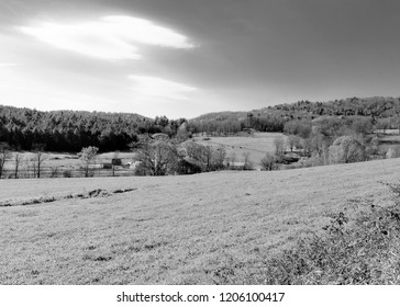 Black and white landscape photograph of the rolling hills of a rural farming countryside with pastures and meadows.