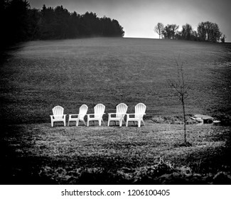 Black and white landscape photograph of rural farming countryside with a set of white lawn chairs in front of a large hillside pasture.