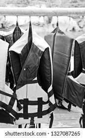 Black and white life jacket hang on metal rack for safety when in the boat