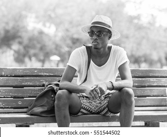 Black and White lifestyle fashion portrait. Stylish young african man sitting alone on a park bench wearing sunglasses and wicker hat.