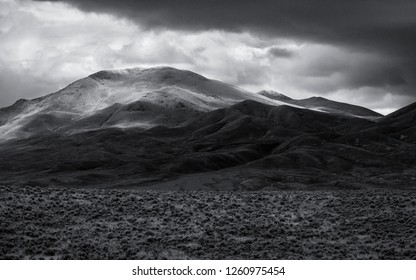 Black and white of light and shadows on mountains in Nevada desert with storm clouds in sky and sagebrush in the valley in foreground.