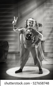 Black and white. Little girl dressed as superhero, she made the V of victory with her fingers. She is in her living room in the middle of a circle of light. Shot with flare