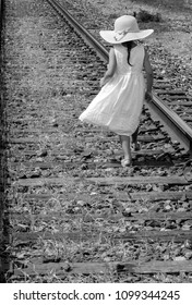 black and white of a little girl in a floppy hat and white sundress walking along a rail road track