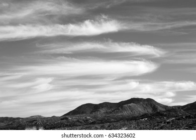Black and white long, cigar-shaped clouds hover over Catalina Mountains in the Tucson, Arizona desert