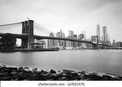 Black & White long exposure shot of the Brooklyn Bridge and New York skyline across the East River on a cloudy summer morning.