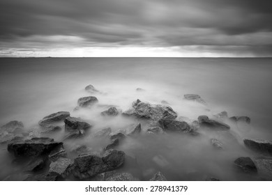 Black and white long exposure shot of rocks on the overcast day on the Gulf of Finland near Saint - Petersburg, Russia.
