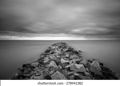 Black and white long exposure shot of rocky path on the overcast day on the Gulf of Finland near Saint - Petersburg, Russia.