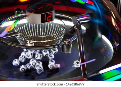 Black and white lottery balls in a rotating bingo machine. Lottery balls in a sphere in motion. Gambling machine and euqipment. Blurred lottery balls in a lotto machine. Number 12.