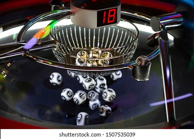Black and white lottery balls in a rotating bingo machine. Lottery balls in a sphere in motion. Gambling machine and euqipment. Blurred lottery balls in a lotto machine. Number 18.