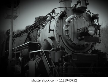 Black and white low angle front view of steel 1800s steam train engine next to railroad signal