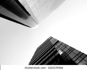 Black and white low angle view of two vibrant blue skyscrapers with reflective glass mirror taken in business environment standing in symmetry facing each other diagonally with bright sky above