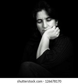 Black and white low key portrait of a beautiful and sad hispanic woman isolated on black