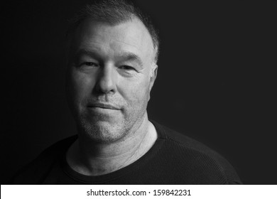 Black and white low key portrait of middle-aged man