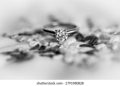 Black and white macro picture of beautiful new shiny white gold engagement ring with big round diamond, placed on the embroidered fabric, blurred background