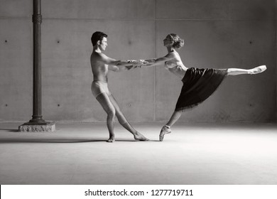 Black and white male ballet dancer supporting holding female dancer in stretching pose lifting leg, trust support control coordination on stage, indoors. Concept harmony power control, teamwork.