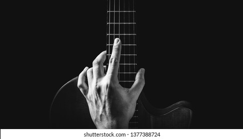 black and white male musician hand posing on guitar, isolated on black, music background