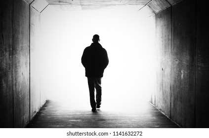 Black & white male person figure in a tunnel walking heading towards a bright light. Concept of death, dying, afterlife, moving on, transition, heaven, suicide, depression, male mental health issues.